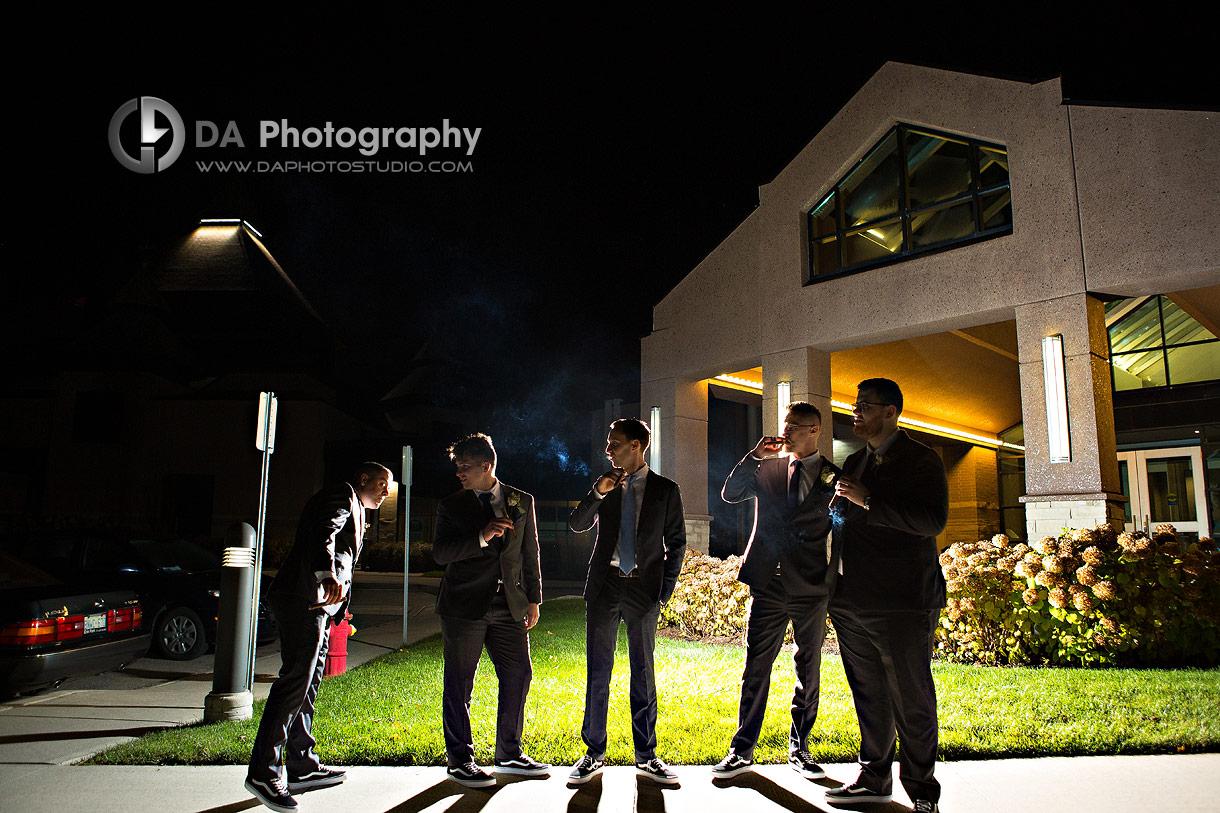 Nighttime portrait of Groomsman smoking cigars